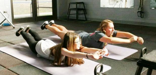CCHS military students Michayla Medley and Kara McVeigh are holding the Superman pose in a Fort Hood gym during the CYSS quarterly FRIENDS meeting. Soldiers put nearly a dozen CCHS students through rigorous physical exercises.