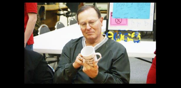 CCISD PHOTO/ JASON MCGUIRE - CCISD Board of Trustees member Mike Wilburn admires the custom-designed coffee mug presented to him by the Crossroads High School student council. Board members were welcome for a luncheon at the school in honor of national School Board Recognition Month.