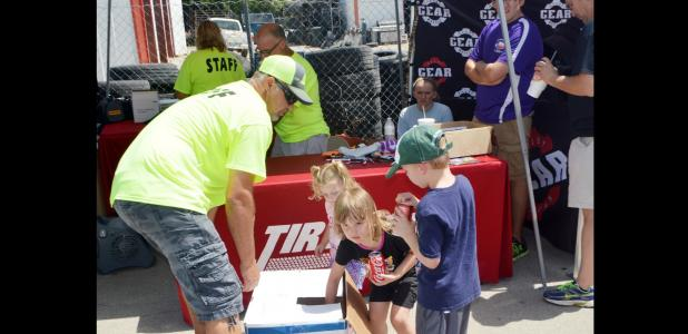 CCLP/LYNETTE SOWELL - Children draw names for door prizes on Saturday at Hank's Tire & Muffler. The threeday customer appreciation event featured a car show, free food, door prizes and giveaways, among them a $500 tire voucher, with no purchase necessary to enter.