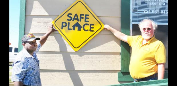 CCLP/DAVID J. HARDIN - Copperas Cove Soup Kitchen director Patrick Richardson and Kelly Jenkins of Central Texas Youth Services hold up the new Safe Place sign, which designates the soup kitchen as a place where at-risk youths can go if they are in trouble and need.