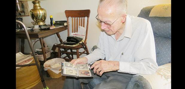 CCLP/BRITTANY FHOLER - Victor Krempin admires photos in his wallet of his wife and daughters, pointing out one where his wife is posing with their eldest daughter, in his home on Oak St.