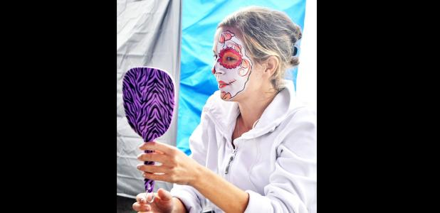 CCLP/LYNETTE SOWELL - A woman inspects her face painting design done by T-Rox Designs at Saturday's Calaveritas Festival at Central Texas College. The annual Dia De Los Muertos event featured vendors, food trucks and a costume contest.