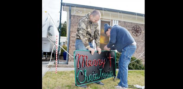 CCLP/LYNETTE SOWELL - Christian Mulvey, with the help of his son-in-law Dustin Phipps, installs a sign that's part of a Christmas lights display synchronized to music. Mulvey will have his 3rd annual light display, this year he is accepting donations for Hope Pregnancy Center.