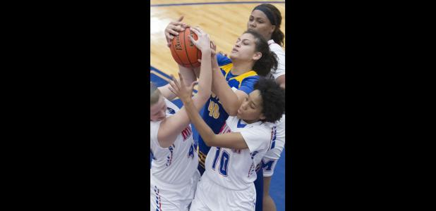 CCLP/TJ MAXWELL - Cove senior Dejhana Butler fights for a rebound in a crowd of Midway defenders during their 60-44 loss Tuesday in Waco. The Lady Dawgs return to action tonight at home against San Angelo Central.