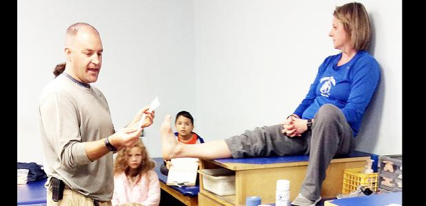COURTESY PHOTO - CCISD athletic trainer Nathan Williams shows second grade gifted education students how to wrap an ankle. Smith taught the students about common injuries and how to treat them, what knowledge of the body a trainer needs, what steps a trainer takes while making a decision about treatment, and when a player is allowed to play again
