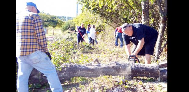 CCLP/LYNETTE SOWELL - Mike Blount and Brian Hawkins cut up a tree at the Sunshine Home apartments on Saturday as part of Make A Difference Day.