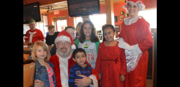 CCLP/LYNETTE SOWELL - Jessica Centunzi-Sanchez, as Mrs. Claus, and Phillip Imergoot, as Santa Claus, pose with kids at Saturday morning's pancake breakfast fundraiser for Relay For Life Lampasas-Copperas Cove at Applebees. Sanchez is the event team leader for Lampasas, and Imergoot is part of the Copperas Cove event team.