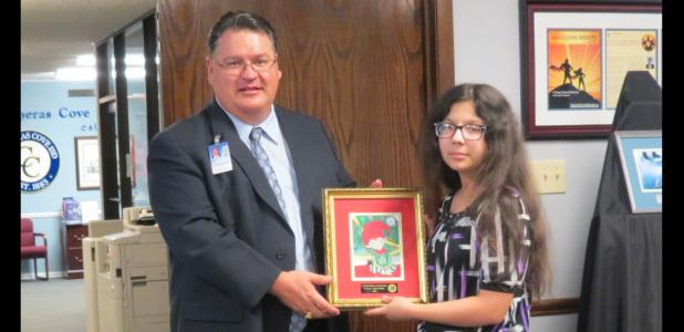CCLP/BRITTANY FHOLER - CCISD Superintendent Dr. Joe Burns presents Alyssa Walker, a 7th grader at S.C. Lee who won 3rd place in the CCISD Holiday Card contest, with her framed card.