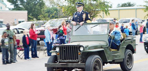 "CCLP/LYNETTE SOWELL - World War II veteran and Pearl Harbor survivor Ret. 1SGT Henri ""Hank"" Grenier stands in a military jeep as he makes his way through the parade route, Friday."