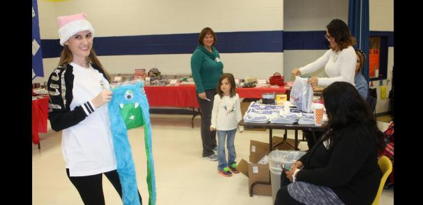 COURTESY PHOTO - Martin Walker Elementary parent Amanda Sawyer volunteers at the school's Peppermint Village Christmas Store to help students pick out gifts for their family and friends.