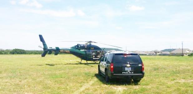 COURTESY PHOTO - A helicopter pilot was using the open green space at House Creek Elementary School to land in a non-emergency situation. In this photo, a Copperas Cove police department officer parked a department SUV beside the helicopter to speak to the pilot.