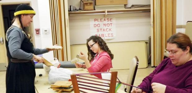 CCLP/PAMELA GRANT - Amy Terry works on her Inkle loom while Wendy Marsh shows Madisyn Pigg how to card wool at the medieval workshop hosted by the SCA at the Copperas Cove Public Library.