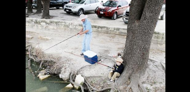 File Photo - Anglers try their luck at the City Park pond. This year's Fishin' in the Park is set for tomorrow from 9-11 a.m.