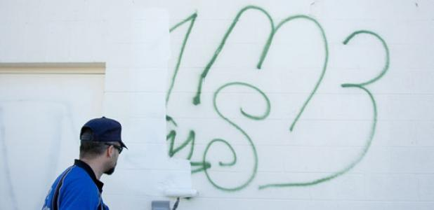 Senior code compliance officer, Beau Brabbin, paints over a gang tagging left on the rear of Mighty Mart Jan. 28. With the help of volunteers the tagging and profanity were covered at no cost to the store that opened at the end of 2013.