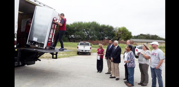 CCLP/PAMELA GRANT - Clarence Enochs, Josh Alvarez, Debbie Peredo, Angie Sargent, Bo Roldan, and Mayor Frank Seffrood watch as a new freezer is delivered to the Cove Meals on Wheels program.The new appliance was donated and will double the amount of people that the group is able to help.