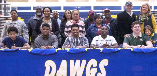CCLP/DAVID MORRIS - Copperas Cove football players, from left, Ra'Shaun Henry (Saint Francis - Pennsylvania), Josh Klenclo (Tyler Junior College), Antonio Lealiiee Texas A&M-Commerce), Shamad Lomax (New Mexco State) and J.P. Urquidez (Baylor) pose with family members during Wednesday's signing ceremony in Bulldawg Gymnasium.