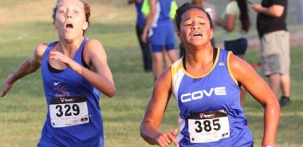 Copperas Cove sophomore Amber Boyd, right, races past Temple's Ashley Raynard on her way to a second place finish during the Temple Invitational cross country meet Friday at Temple Lions Park.