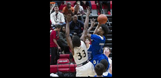 CCLP/TJ MAXWELL - Cove sophomore Quinton Ford drives the lane for two points in fron of Lake Travis sophomore D.J. Thorpe during the Bulldawgs' 65-54 loss to the Cavaliers Tuesday in Austin.