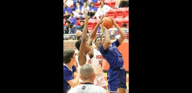 CCLP/TJ MAXWELL - Copperas Cove senior Dahmir Pearson attempts a shot in traffic with Cedar Hill 6-feet-8 sophomore Sammie Freeman and senior forward Xavier Whitaker (4) defending. Pearson led the Bulldawgs' scoring with 14 points, including 12 for 14 free throws.