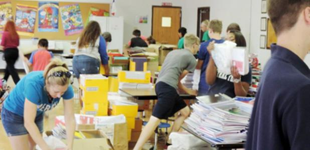 Courtesy Photo - Members from the Excel Club of Copperas Cove High School help empty a bus filled with school supplies collected from the Stuff the Bus project. Over a two month period, Stuff the Bus volunteers collected over $25,000 worth of supplies under the leadership of Rabbit Fest Queen Karagan Mayberry.