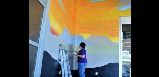 CCLP/LYNETTE SOWELL - Five Hills Art Guild mural project director Sheri Wilson works at blocking areas of the guild's mural at the future Sutherlands Home Base store, set to open in March.