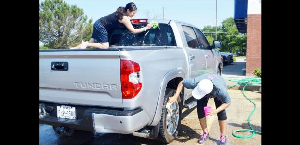 CCLP/LYNETTE SOWELL - Kori Ramos and Kimmie Russell wash down a truck on Saturday morning at Buddy's on Business 190. Pink Warrior Angels washed cars to help the Pride of Cove Band purchase pink plumes to wear with their uniforms for October's Pink Out game this fall.