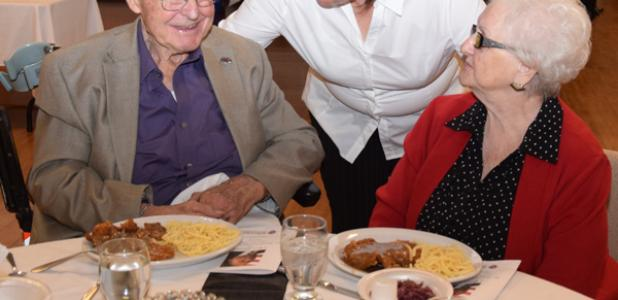 Elizabeth Hayden serves a German style dinner to John Hull and his wife, Shirley Hull, who were in attendance at Saturday's event in MLK's honor.