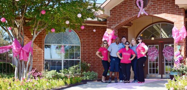 CCLP/LYNETTE SOWELL -- The staff at Clear Creek Meadows Apartments stand in front of their decorated entryway. The business was awarded first place in the Pink Out The Town contest held by Pink Warrior Angels.