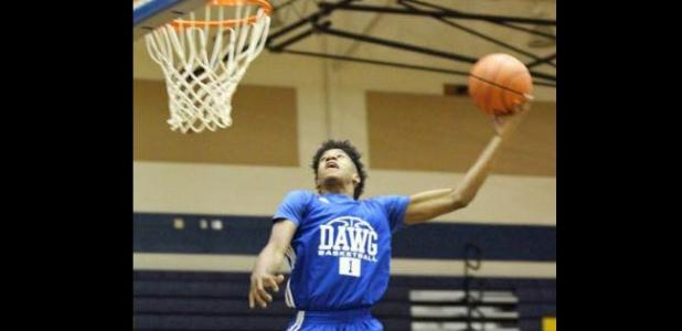 Courtesy photo - Cove sophomore Quinton Ford competes in the dunk contest during the annual Meet the Dawgs event
