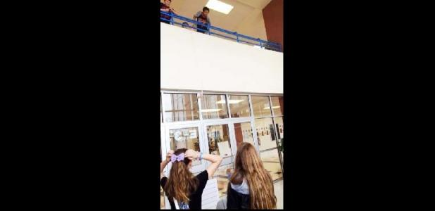 COURTESY PHOTO - S. C. Junior High students launch bungeed Barbie Dolls from the second story inside balcony using rubber bands to gather and graph data on the motion of a falling object as part of a science experiment.