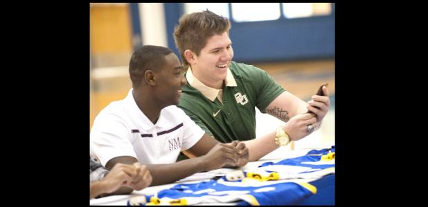 CCLP/DAVID MORRIS - Shamad Lomax, left, and J.P. Urquidez react to a message on Urquidez's phone during Wednesday's signing ceremony. Lomax and Urquidez signed to play for the highest echelon in college football with New Mexico State and Baylor, respectively.