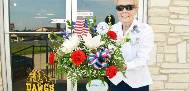 Trudy Bolton leaves A&L Florist on Wednesday morning with a flower arrangement donated by the shop for the funeral of Arthur McClanahan, an unaccompanied veteran who served in the Air Force from 1981-1983.