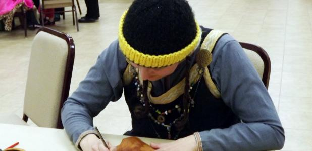 CCLP/PAMELA GRANT - Wendy Marsh works on tooling leather at the medieval workshop hosted by the SCA at the Copperas Cove Public Library. Here she works on finishing off her greaves which will be worn when she participates in rapier fighting.