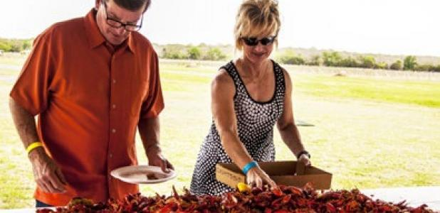 Guests pile crawfish, sausage, corn and potatoes into their boxes at the 7th annual crawfish boil at Texas Lagato winery in Lampasas.