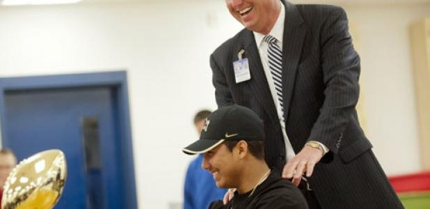Copperas Cove's Deputy Superintendent Rick Kirkpatrick shares a laugh with Elijah Timarky during the signing day ceremony.