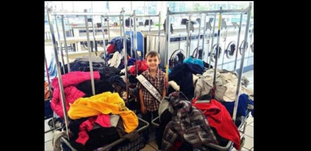 Zachary Petty, Junior Mister Rabbit Fest, stands among the carts of clothing he collected from CCISD campuses' lost and found to donate to the needy.