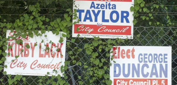 "Campaign signs hang on a fence along Veterans Ave. The word ""for"" on the signs has become a hot topic between the candidates with Lack and Duncan both admitting they inadvertently left off the word."