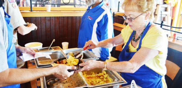 April Fitzgerald serves up eggs at Saturday's flapjack fundraiser held by the Rotary Club at Applebees on Saturday.