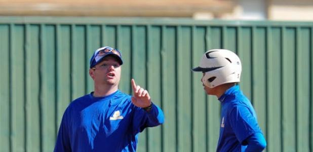 First year Bulldawgs coach Dusty Brittain talks with one of his players as they participate in the scrimmage at Gateville High school. BELOW: Brittain watches as the Dawgs take their turn at bat in the scrimmage.