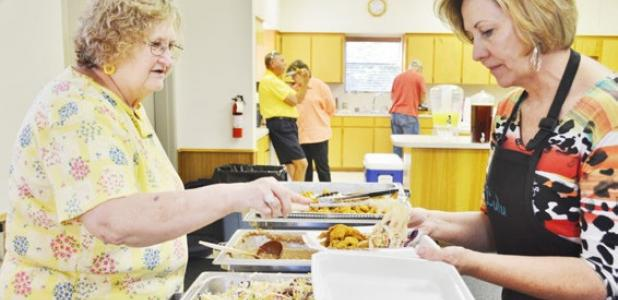 Margaret Martin, left, helps Lulu Maples prepare a boxed catfish and brisket meal at Pidcoke United Methodist Church's Big Feed on Saturday.