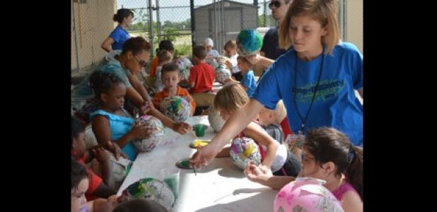 Camp Discovery counselor Hailey Hensley gives the Roadrunner campers a hand with their paper mache balloons.
