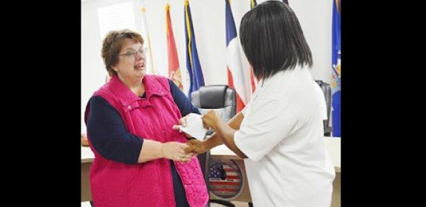 Mae Stevens Early Learning Academy principal Mary Derrick accepts a donation from the Star Group Veterans organization Saturday during the monthly meeting.