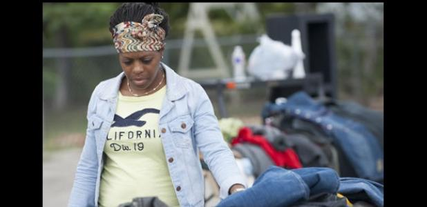 Esha Cole, browses through piles of clothes as she visits the Bountiful New Life Church of God in Christ's final garage sale in the parking lot off Ave. E, Saturday.