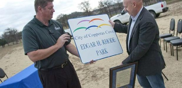 Parks and Recreation director Joseph Pace presents Brett Rhode with a copy of the sign of the park that bears his fathers name. Edgar H. Rhode Park is open for play and currently has an open field for soccer.