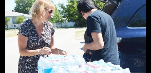 Silvia Rhoads, left, gets some help unloading 10 cases of water at Cove House on Monday afternoon, as part of her Ice Bucket Challenge.