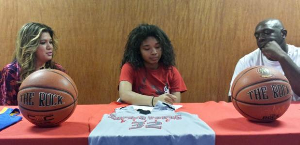 Copperas Cove senior guard Xylina Carlisle, center, with her parents Rose and Orlando Carlisle recently signed a letter of intent to play basketball for the Sul Ross Lady Lobos.