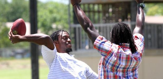 "Heisman trophy winner and Washington Redskins quarterback Robert Griffin III, throws a pass as Charles ""Peanut"" Tillman defends during the filming of a commercial for USAA (United Services Automobile Association) on Wednesday at Copperas Cove High School."