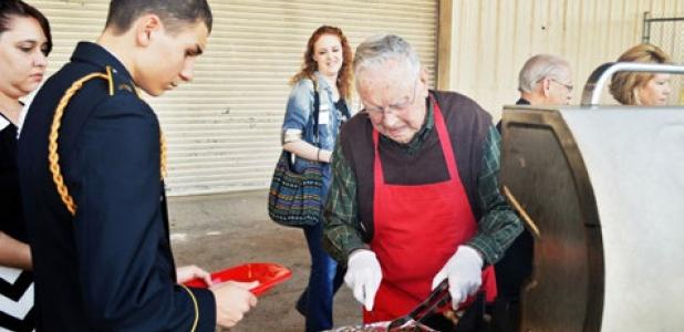 Woody Shemwell, one of seven grill volunteers, checks a steak at Thursday night's military affairs banquet hosted by the chamber of commerce.