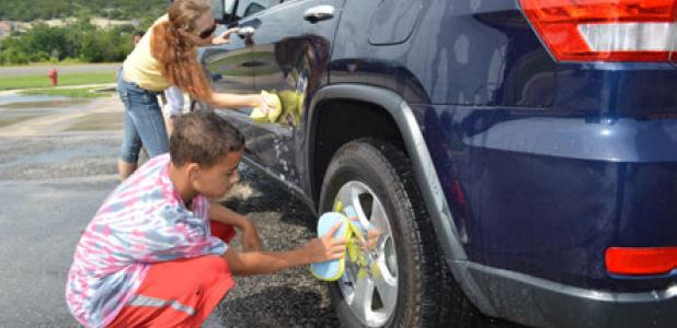 Stephanie Burkholder and Shannon Bryant wash a car at Saturday's fundraiser for The Rainbow Room.