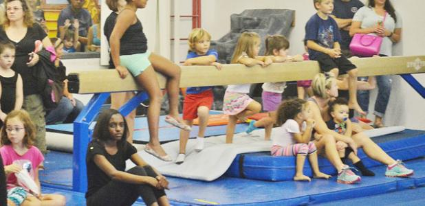 Children of all ages watch the gymnastics demonstration at Saturday's National Gymnastics Day celebration.
